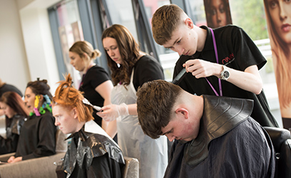 Image of a group of hairdressing students cutting clients hair