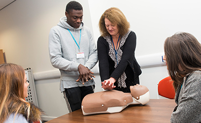 photo of tutor demonstrating CPR on a dummy
