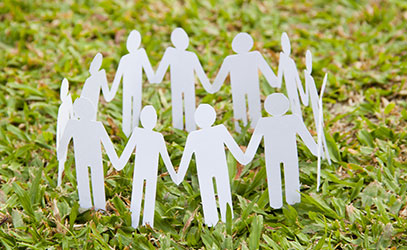 photo of paper people holding hands in a circle on the grass