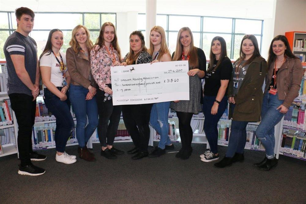 Proud students presented Framework's Abbi Mayfield (4th right) with their generous cheque